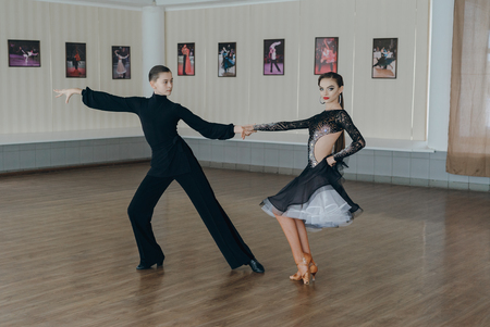 dancing man: Professional dancers dancing in ballroom. Latin. Young boy and girl Stock Photo