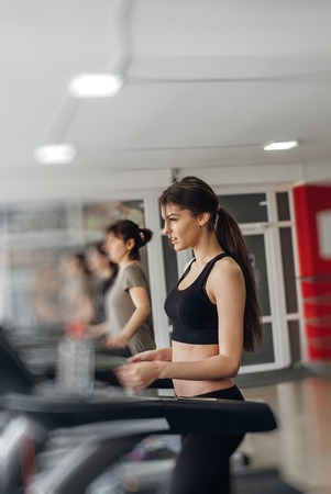 Beautiful group of young women friends  exercising on a treadmill at the bright modern gym Reklamní fotografie