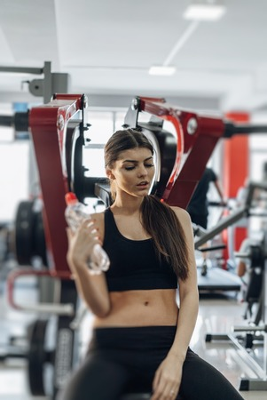Portrait of cheerful young attractive woman with bottle of water, at fitness club or gym. Gym