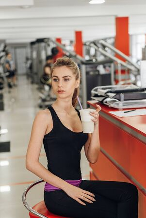 A beautiful young woman sitting at the gym and drinking protein. Reklamní fotografie