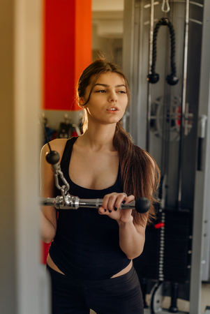 Sexy athlete woman lifts in the gym. Brunette performs an exercise on the sports simulator
