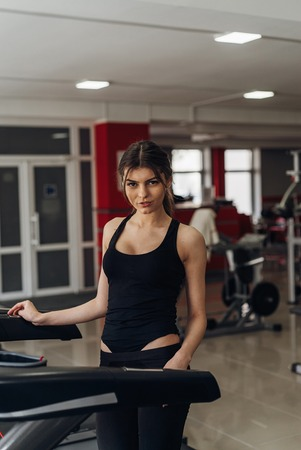 Gym. Sexy brunette exercising on treadmill. Run