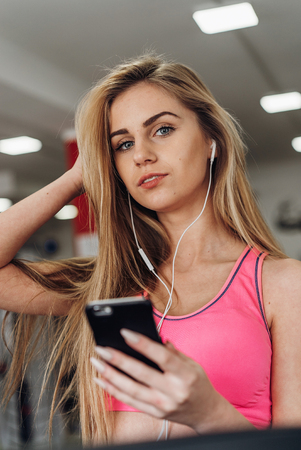 Young woman listening to music with earphones on smart phone app for fitness motivation. Athlete runner in sportswear relaxing sitting getting inspired.