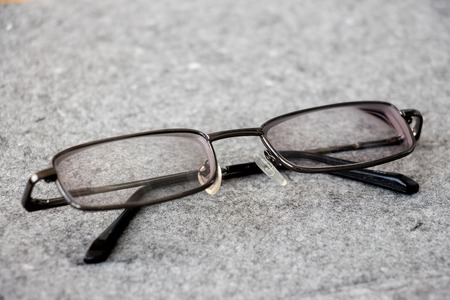 soundness: Mens glasses with a thin rim on a gray background closeup. Glassess in the folded state