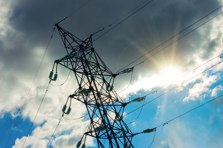 A high voltage power pylons against blue sky. The photo shows a blue sky with cloud through which the sun shines Stock Photo