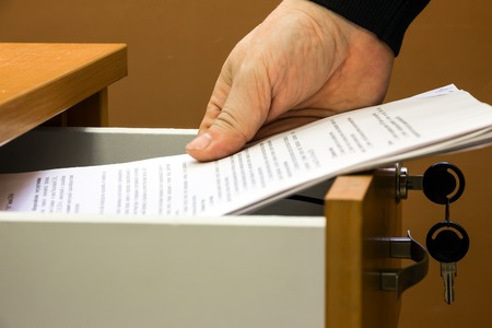 Man puts or takes the documents from the drawer Stock Photo
