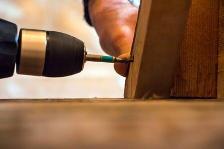 screwing: Man Screwing a screw into the wood