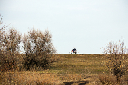 Motorcyclist rides on the road against the sky