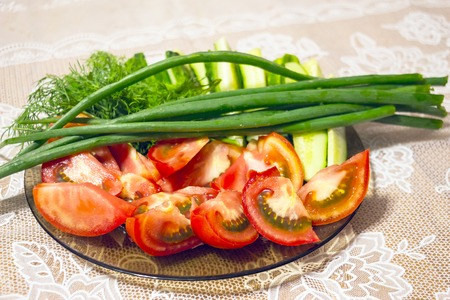 Sliced tomatoes and green onions on a plate. Fresh vegetables