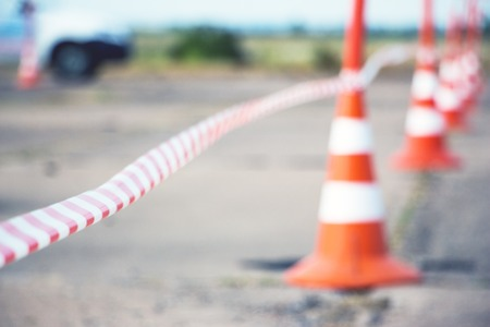 Selective focus. Fencing tape and road cone Stock Photo