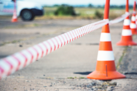 Selective focus. Fencing tape and road cone Standard-Bild