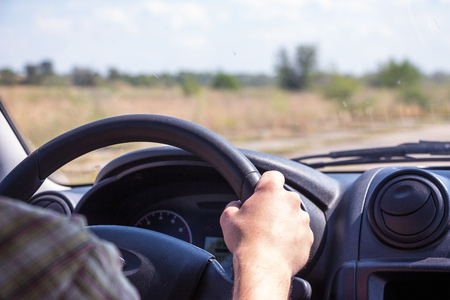 Men hands on the wheel of a car. Stock Photo