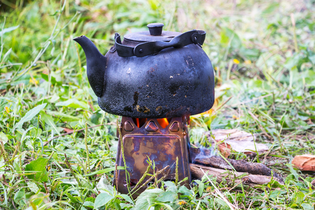 The smoked kettle is heated on the camp portable stove Stock Photo