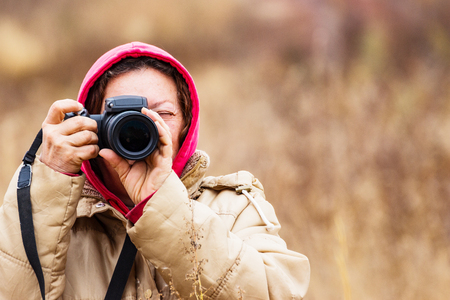 Female photographer looking through the viewfinder of the camera. The woman is dressed in a jacket and hood. On the street the cold season