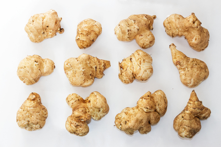 inulin: The tubers of Jerusalem artichoke are set in rows on white background Stock Photo