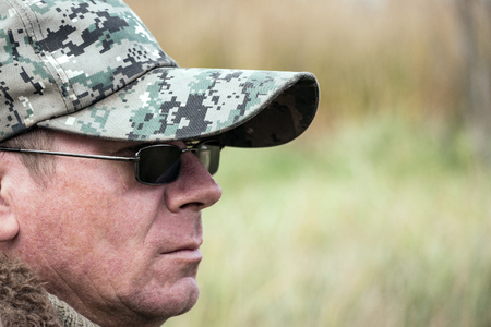 Portrait of a brutal man. The man in dark glasses, a warm sweater and a cap Stock Photo