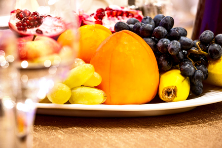 Still life. Fruit in a plate on the table. Pomegranates, apples , bananas, grapes and persimmons