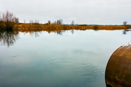 Autumn lake with a Autumn lake with a pipe from which the slowly flowing water. Late autumn