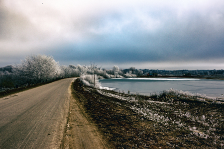 Landscape with a road and a lake. Late autumn, early winter
