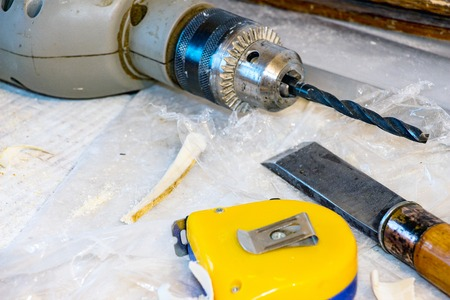 A carpenters tool. Drill chisel measuring tape