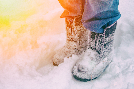 Woman in jeans and in felt boots standing in the snow