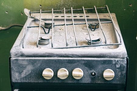 An old dirty gas stove in an abandoned state. Unsanitary conditions