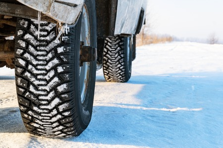 Studded winter car tires on snow-covered road Stockfoto - 95565657