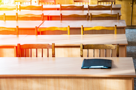 Empty tables in the classroom. On the table is a folder