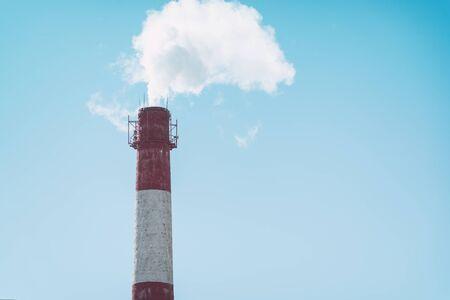 The smoke from a factory chimney on background of blue sky