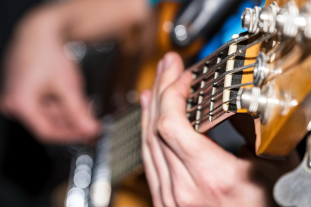 Hands and fingers of the guitarists bass on the fretboard close-up. Plays bass guitar. Selective focus