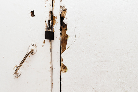 Small closed lock on an old white door Stock Photo