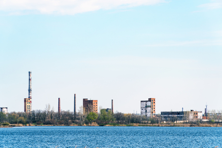Old Abandoned chemical factory with chimneys on the banks of river