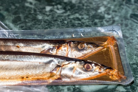 Sea fish saury in vacuum packaging on the table. Selective focus
