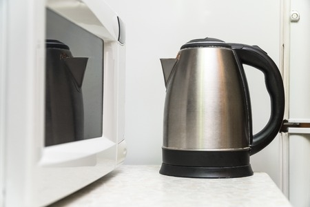 Electric kettle and microwave on the kitchen table. Kitchen utensils Stok Fotoğraf