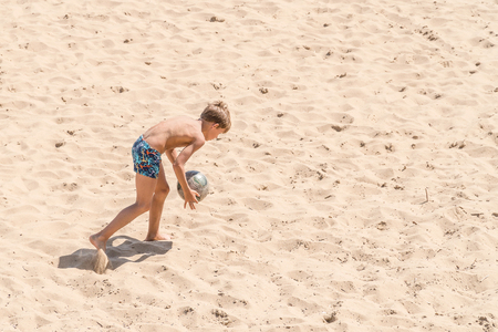 SAMARA, RUSSIA - JUNE 21, 2018: Boy playing soccer on the beach