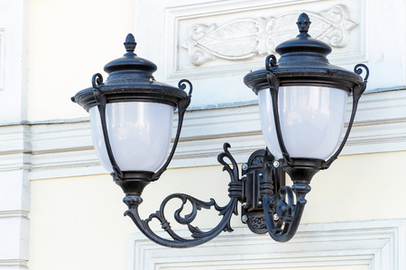 Street lights in the old style on the wall of the house Фото со стока