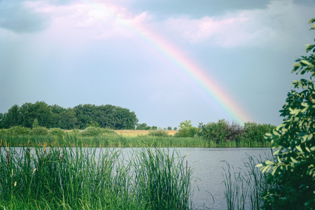 Rainbow over the lake and forest against a cloudy sky
