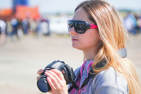 Samara, Russia - August 18, 2018: Unfamiliar girl in sunglasses with a camera