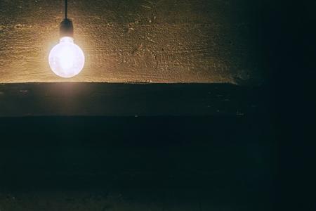 Light bulb in the room against the dark ceiling. Soft focus 免版税图像