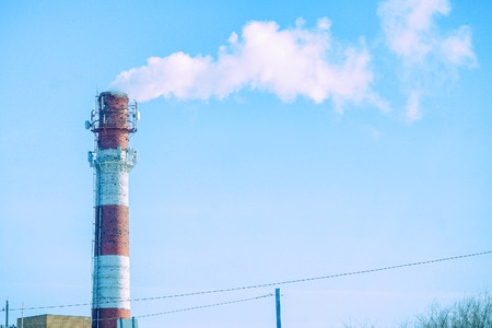 The smoke from a factory chimney on background of blue sky Standard-Bild - 120264113