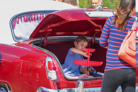 Samara, Russia - August 18, 2018: Girl plays sitting in the trunk of a car Éditoriale