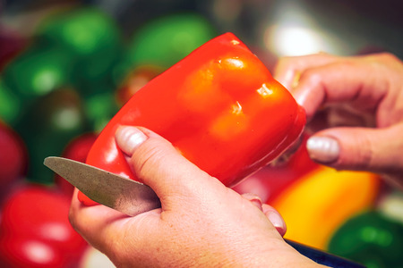 Holds in hands a bell pepper. Cuts with a knife red bell pepper
