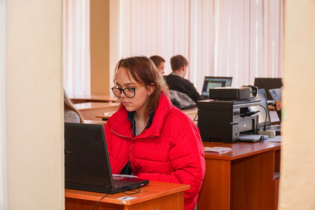 Chapaevsk, Samara region, Russia - April 17, 2019: College in Chapaevsk city. Girl student in front of the computer in the computer class