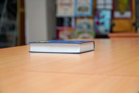 A closed Book on a wooden table on a background of blurred bookshelf