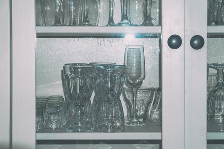 Clean empty wine glasses on the shelf in the cupboard. Soft focus
