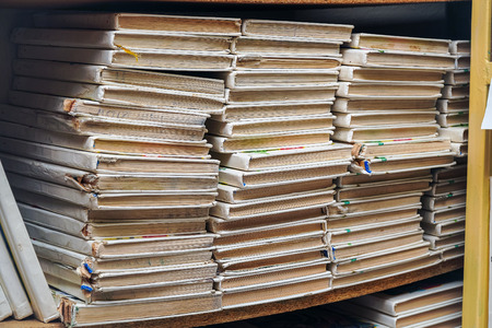 Old books in stacks on the shelf. Wastepaper