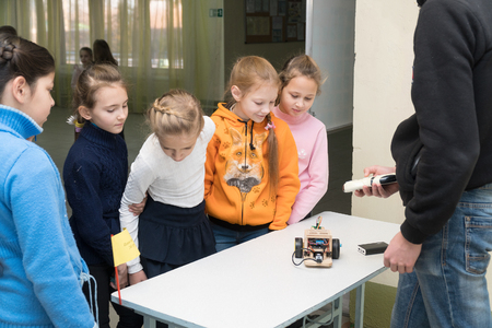 Chapaevsk, Samara region, Russia - November 16, 2018: Primary School in Chapaevsk city. Schoolgirl girls are smiling and looking at a homemade car model