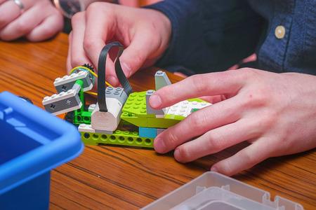 Le garçon fait un modèle de voiture à partir des détails du designer pour enfants