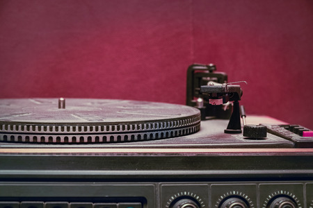 Old record player on red background. Selective focus