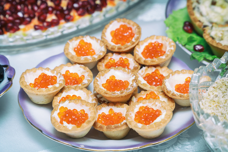 Tartlets with red caviar on a plate. Selective focus